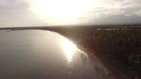 Sun que ajusta-se sobre o Sandy Beach tropical vazio e o mar calmo bonito no dia nebuloso, vídeos de arquivo