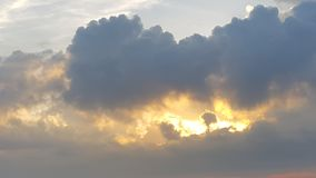 The Sun que brilha atrás da nuvem escura enorme, grossa Fotografia de Stock Royalty Free
