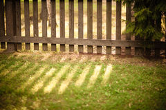 Sun que brilha através da cerca de madeira imagem de stock