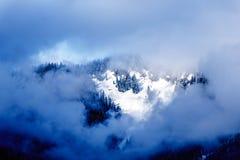 Sun que brilha através das nuvens na neve tampou o pico da montanha de Coquitlam nas montanhas da costa Imagem de Stock