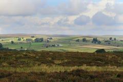 Sun que brilha através das nuvens nos campos, North Yorkshire Fotografia de Stock