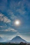 Sun que brilha em uma paisagem das árvores e das montanhas em um céu azul Fotografia de Stock Royalty Free