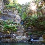 Sun que brilla con la cascada en el bosque Foto de archivo libre de regalías