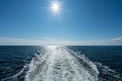 Sun que brilla sobre la estela del barco de cruceros en el mar Imagenes de archivo