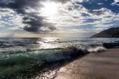 Sun que brilla a través de las nubes en la playa arenosa con las ondas fotos de archivo