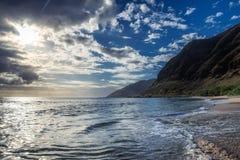 Sun que brilla a través de las nubes en la playa arenosa con las ondas imagen de archivo libre de regalías