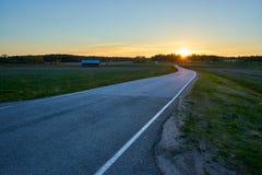 Sun que estabelece atrás dos campos e da estrada vazia imagens de stock