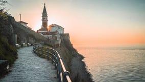 Sun que fija detrás de la torre de reloj en la ciudad de la playa de Piran, Eslovenia foto de archivo libre de regalías