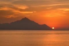 Sun que mira a escondidas sobre la montaña y el horizonte de mar Fotos de archivo