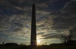 Sun que move-se atrás de Washington Monument cercou por bandeiras dos E.U. contra o céu azul fotos de stock royalty free