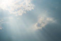 Sun que proyecta rayos detrás de las nubes dramáticas en el cielo azul antes de una tempestad de truenos Foto de archivo