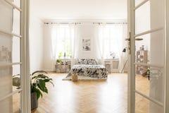 Sun que shinning através das janelas em um interior à moda espaçoso do quarto em uma casa de campo Cama grande com o fundamento q foto de stock royalty free