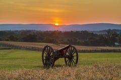 Sun que sube detrás de artillería cerca de un campo de trigo en Antietam Foto de archivo libre de regalías