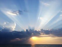 Sun quebra no alvorecer devido às nuvens sobre o mar imagem de stock