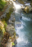 Sun a quick dip in the mountains. Rapid mountain river falls down the mountain. It has a turquoise color. Sunny day, Bright colors. The beautiful nature of the Stock Image