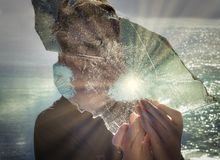Sun-raggi che riflettono sul ghiaccio in mani del ragazzo fotografia stock