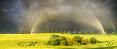 Sun, rain and two rainbows over the field Stock Photo