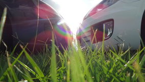 Sun rainbow grass in focus cars in background nose to nose black and white. Low car hatchback night river boats no filters natural rainbow Stock Images