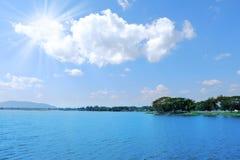 Sun ray light on blue sky over big lake background. Sun ray light on blue sky over big lake nature background royalty free stock image