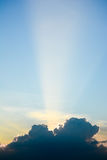 Sun ray shine through dark cloud in the sunrise sky. Royalty Free Stock Images