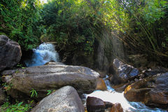 Sun ray and water fall. A tropic waterfall with rock and stone with sun beam Stock Photos