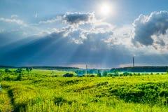 Sun rayonne au ciel de tempête sous une vallée photos stock