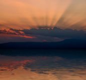 Sun rays. Sun behind the cloud with sunrays and reflection in water Royalty Free Stock Photos