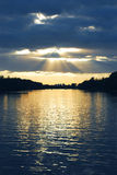 Sun rays. Rays of sun shining through the clouds and sunset over water Royalty Free Stock Images