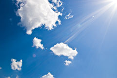 Sun rays. On blue sky with white clouds Stock Photography