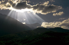 Sun rays. And clouds over the mountains landscape Stock Photos