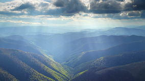 Sun rays above the slopes of mountains. Heavenly sun rays fall through the clouds on the slopes of Carpathian Mountains stock video footage