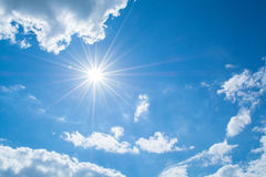 Sun rays against a blue sky in the clouds. Stock Photo