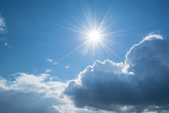 Sun rays against a blue sky in the clouds. Royalty Free Stock Images