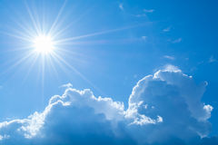 Sun rays against a blue sky in the clouds. Stock Photography