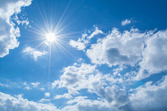 Sun rays against a blue sky in the clouds. Stock Photos