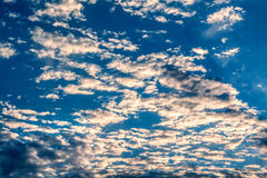 Sun rays against a blue sky in the clouds. Royalty Free Stock Photos