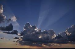 Sun rays attraverso le nubi ad un tempo di tramonto Fotografia Stock