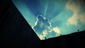 Sunrays from behind the cloud on a sunny day with sunny sky and clouds. Sunrays from behind the clouds Royalty Free Stock Images