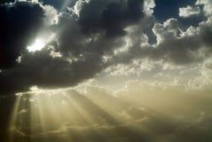 Sun rays behind clouds stock photos