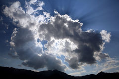 Sun rays behind clouds above mountains Stock Photos