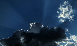 Sun rays behind stormy clouds Royalty Free Stock Image