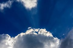Sun rays on blue sky with clouds. Image of the sky with some clouds and sun rays getting through. Blue sky with rays of light and fluffy clouds Stock Photography