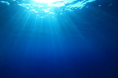Sun rays in blue water Stock Images