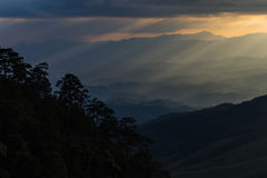 Sun rays breaking through the clouds over a mountain landscape Stock Images