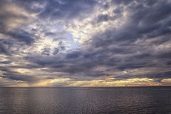 Sun rays breaking through the clouds over the sea. White and golden sun`s rays make their way through the storm clouds over the sea Stock Photography
