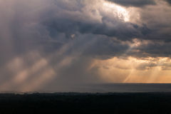 Sun rays breaking through rain clouds Stock Images