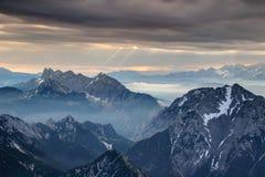 Sun rays burst through dark gray clouds over misty jagged peaks stock photos