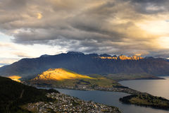 Sun rays is bursting thru thick clouds and illuminate some part of the mountains. Stock Photo
