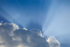 Sun rays through cloud above clear blue sky. Beautiful sun rays through cloud above clear blue heaven sky, sunlight in the summer day Royalty Free Stock Photo