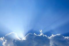Sun rays through cloud above clear blue sky. Beautiful sun rays through cloud above clear blue heaven sky, sunlight in the summer day Stock Photography